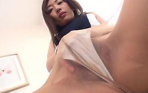 Asian minx in toffee-nosed heels and pantyhose masturbates on the top of a chair